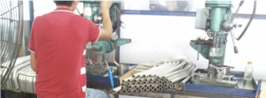Chinese factory operator drilling with parts stacked to hand