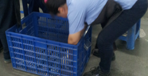 Chinese factory operator reaching into large box